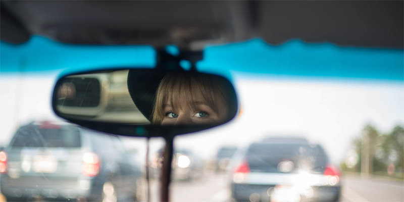 Chica mirando por el retrovisor