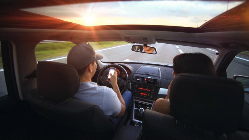 multas en verano, conductor mirando el móvil