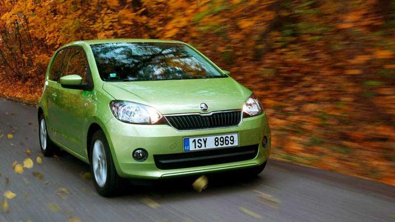 un coche de color verde claro que está en marcha con hojas secas en la parte derecha