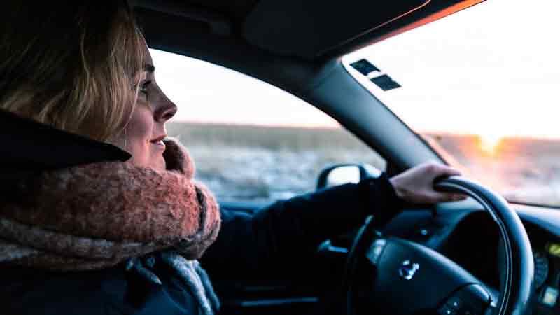 Chica conduciendo un Volvo de día