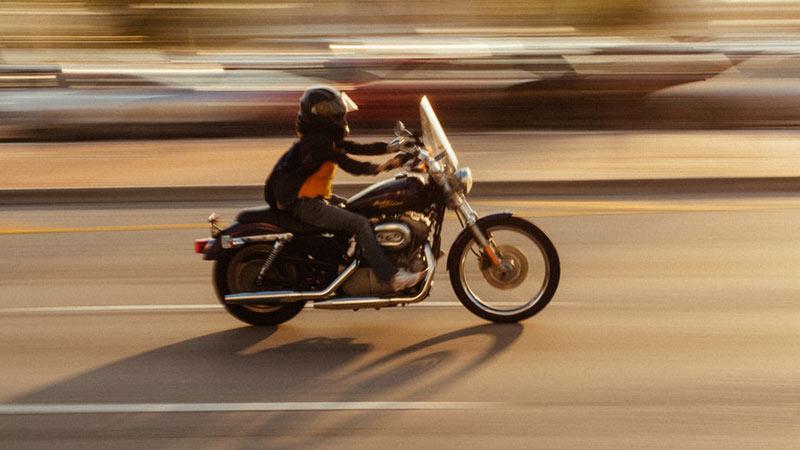 Conductor de moto a toda velocidad por la carretera, se difumina el fondo