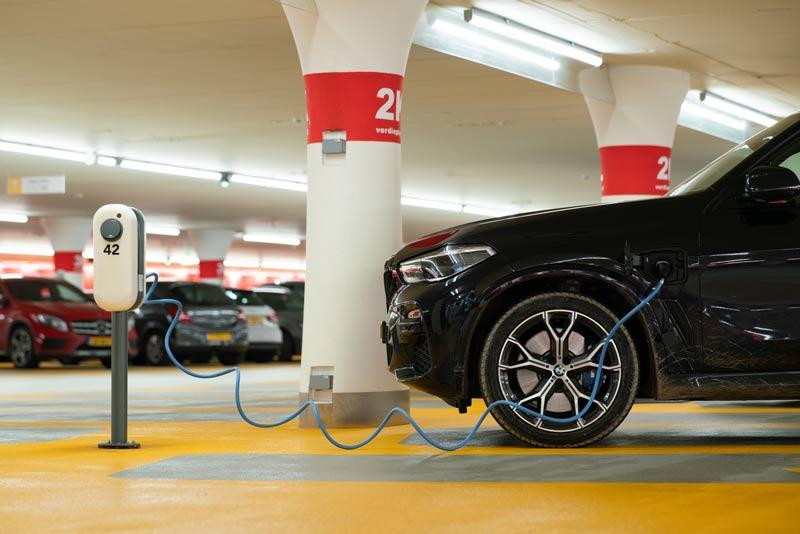 Recarga de un coche eléctrico negro en un garaje con suelo amarillo