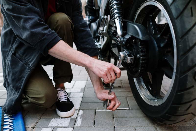 Manos de un chico arreglando una moto con una llave inglesa