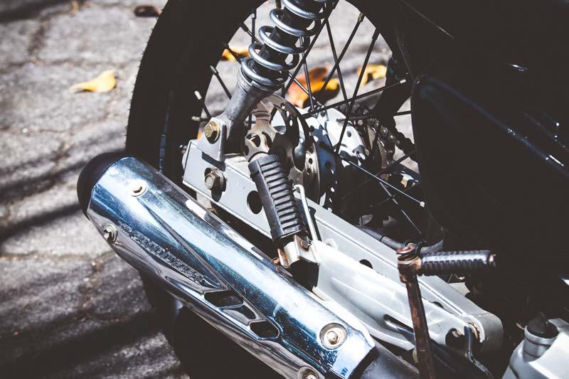 Rueda y tubo de escape de moto sobre asfalto con hojas